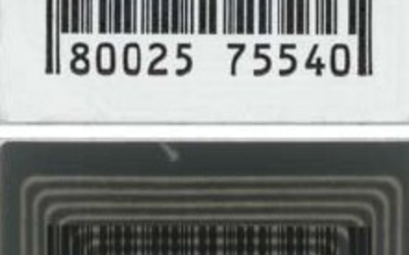 A bar code, shown at top as a reflective print and below illuminated as a transparency. This small inventory device, this one from a bookstore, contains in the dark central area a hidden picture, which, unless it is disabled during checkout, can be read electronically to alert the store that a product is being removed illegally.