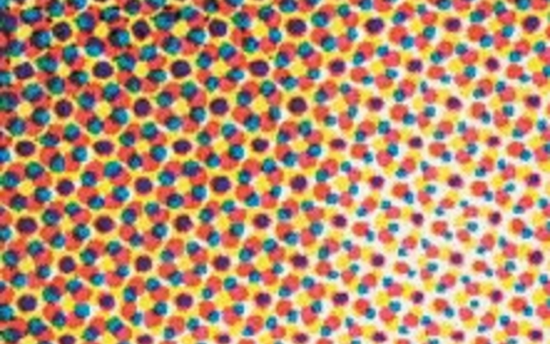 In any multiple-screen print—one that uses more than one dot pattern—some dots are next to each other and some are on top of each other. If the inks are transparent, their respective locations make no difference to the eye of the viewer when seen at a normal viewing distance. This detail shows the basic pattern of four-color process printing using traditional halftone screens.
